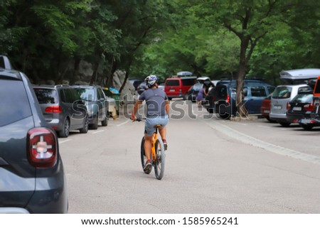 PAKLENICA, CROATIA - 08/02/2019: Man riding a bicycle through a car park in front of Paklenica national park. #1585965241
