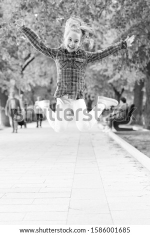 Tireless and energetic activity. Small child jumping in casual fit for physical activity. Active child enjoying playing activity in summer park. Little kid dressed for childhood outdoor activity. #1586001685