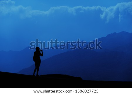 Young tourist woman standing on top of mountain and looking at a beautiful landscape. Adult girl tourist relax on hill in summer epic sky up view. High peak tour Classic blue 2020 year color concept