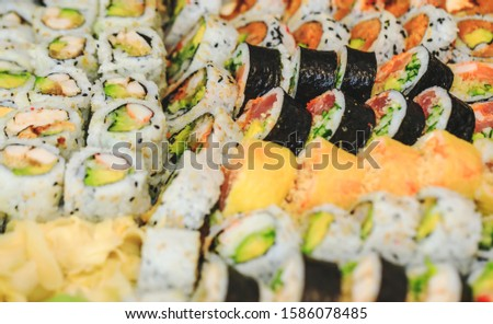Sushi rolls with salmon, avocado, tuna and cucumber. Fresh maki with rice and nori. Delicious Japanese food with sushi roll in close up picture. Healthy kale and sushis. Holiday food setting.