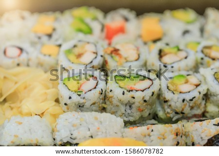 Top view if sushi rolls with salmon, avocado, tuna and cucumber. Maki plate with rice and nori. Delicious Japanese food with sushi roll in close up picture. Healthy kale and sushis. Holiday food table