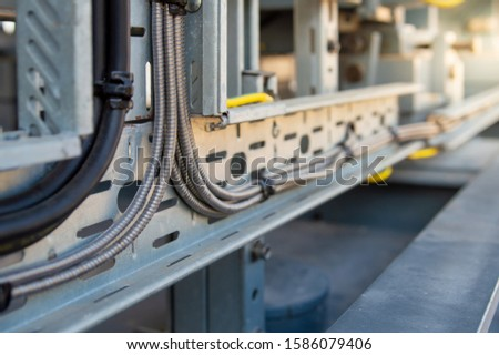 Power cables and instrument cables in the trays .Electric cables lying in metal cable trays.Cable tray and Cable ladder on Pipe Rack. #1586079406