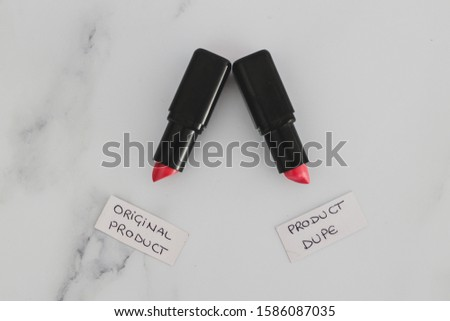 beauty industry competition conceptual still-life, two identhical looking lipsticks with Original Product and Product Dupe labels #1586087035