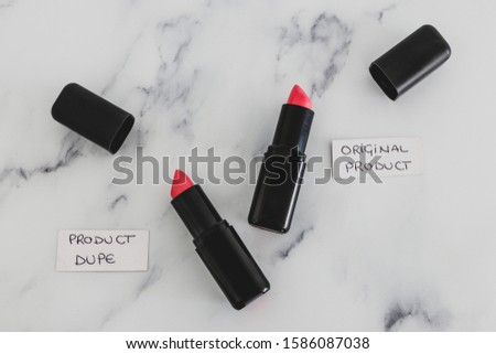 beauty industry competition conceptual still-life, two identhical looking lipsticks with Original Product and Product Dupe labels #1586087038