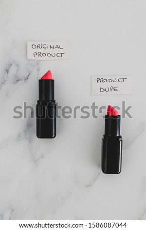 beauty industry competition conceptual still-life, two identhical looking lipsticks with Original Product and Product Dupe labels #1586087044
