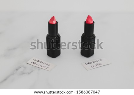 beauty industry competition conceptual still-life, two identhical looking lipsticks with Original Product and Product Dupe labels #1586087047