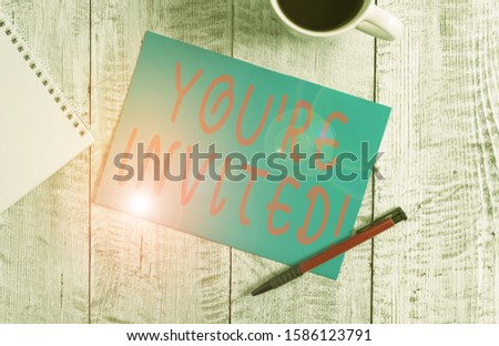 Text sign showing You Re Invited. Conceptual photo make a polite friendly request to someone go somewhere Stationary placed next to a cup of black coffee above the wooden table. #1586123791