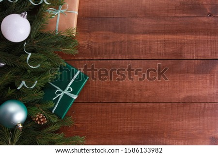 Christmas gifts, white baubles, mint streamer, fir tree branches on dark brown wooden table. Christmas background. New Year, winter holiday, copy space, top view #1586133982