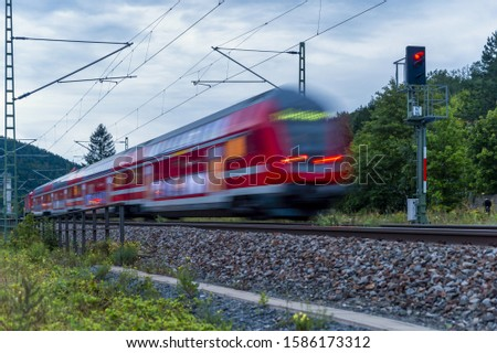 Red regional train with motion blur #1586173312