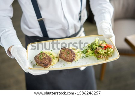The waiter is holding a plate Delicious juicy meat cutlets, mashed potatoes sprinkled with greens and fresh healthy salad of tomatoes and lettuce leaves. #1586246257