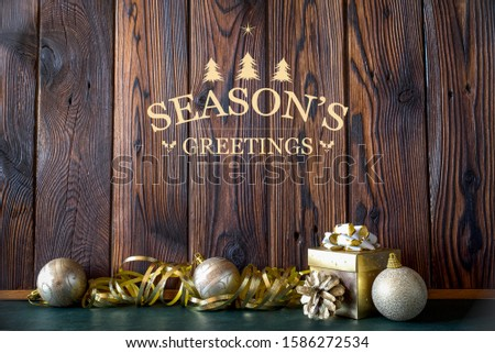 Golden Christmas balls, tinsel tape, gift box, and pine tree cone against a dark brown wooden background with season's greetings text