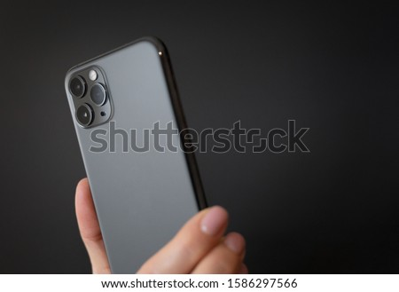 Person holding modern smartphone with triple-lens camera against dark background