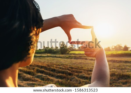 woman hand framing view distant over sunset. business concept Royalty-Free Stock Photo #1586313523