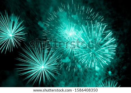 Luxury fireworks event sky show with turquoise big bang stars. Premium entertainment magic star firework at e.g. New Years Eve or Independence Day party celebration. Black dark night background
