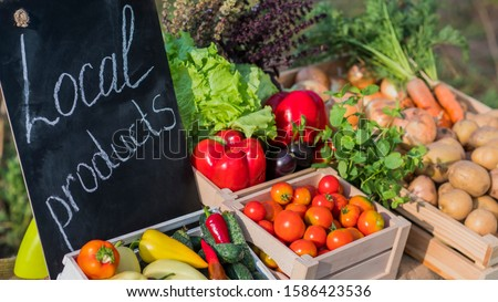 Counter with fresh vegetables and a sign of local products