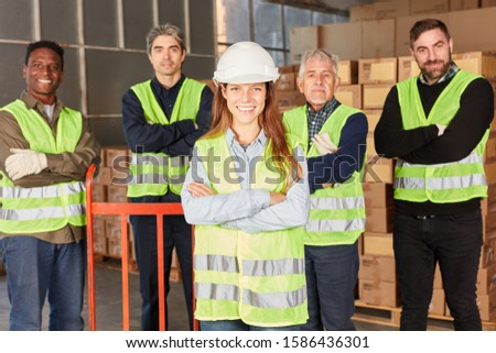 Young woman as a logistics apprentice with her team in the dispatch center of the forwarding company #1586436301