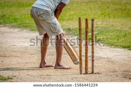 A young Indian boy playing cricket. View of a right handed batsman with all three stumps visible. #1586441224