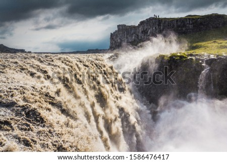 Amazing Dettifoss waterfall  in Vatnajökull National Park in Northeast Iceland. Silhouetts of tourists on the cliff. The falls are 100m wide and have a drop of 44m down to canyon