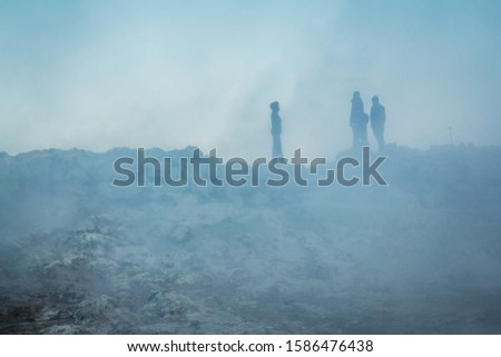 Silhouetts of tourists seen through steam coming from mud holes and solfataras in the geothermal area in Iceland. 