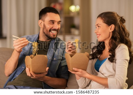 fast food and people concept - happy couple eating takeaway noodles with chopstick at home in evening #1586487235