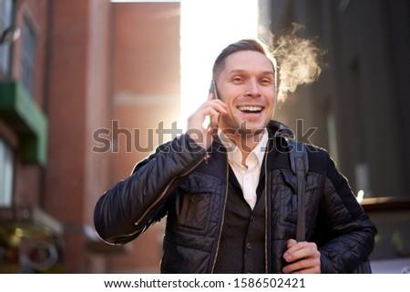 Happy man talking on phone in city against backdrop of modern buildings. #1586502421