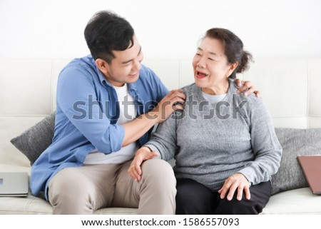 Asian senior grand mother with son happy and smile on the sofa in living room love family concept #1586557093