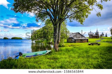 Summer rural village river shore. River boat on shore in village. Village river shore. Village river boat scene #1586565844