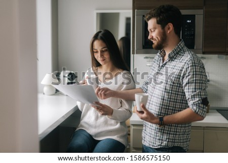 Beautiful couple is reading documents. Daily life of a male and female in apartment. #1586575150