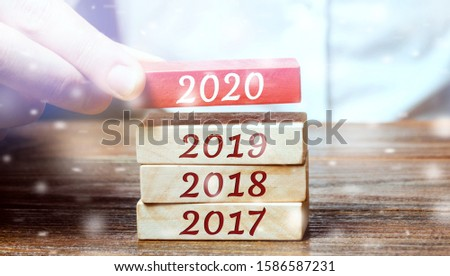 Businessman builds wooden blocks 2020. The concept of the beginning of the new year. New goals. Next decade. Trends and changes in the world. Build plans and planning. Time report. Snow, snowfall #1586587231