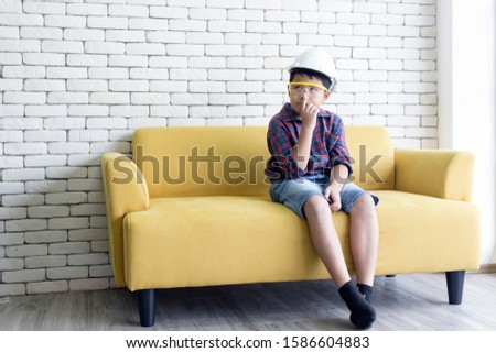 An Asian child engineer was sitting worrying on the yellow sofa. #1586604883