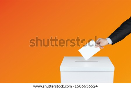Hand of a person use a vote into the ballot box in elections. With orange background                         #1586636524