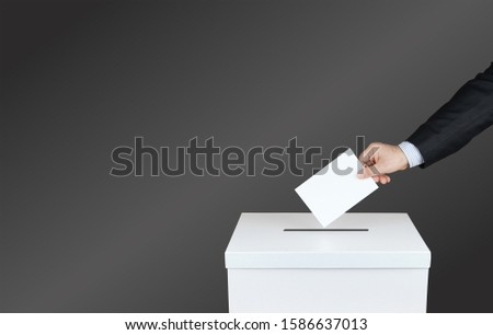 Hand of a person use a vote into the ballot box in elections. With black background       #1586637013