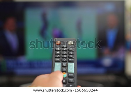 A person with a TV remote controls the remote control to switch channels to watch TV shows. #1586658244