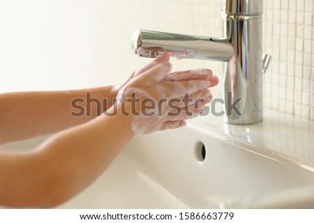 Boy washing hands at sink, Den Haag, Netherlands #1586663779