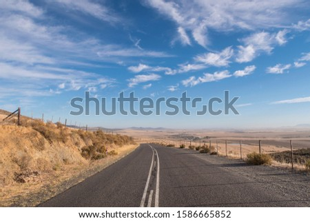 View of long open road at sunrise in arid landscape #1586665852