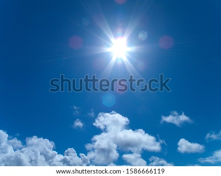Sunbeams shining from sun in blue sky #1586666119