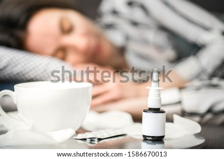 concept of a person suffering from a cold. different items needed for colds - spray and handkerchiefs, a cup of tea and pills, a woman sleeping in the background #1586670013