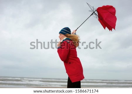 A woman standing on a beach with her umbrella blowing inside out #1586671174