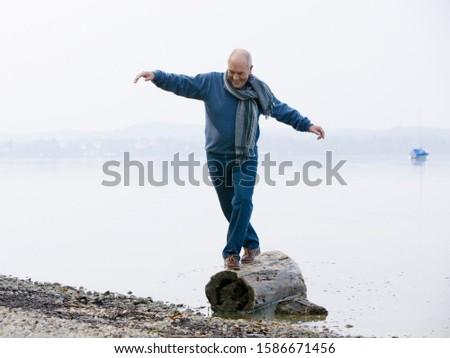 A senior man balancing on a log at the edge of a lake