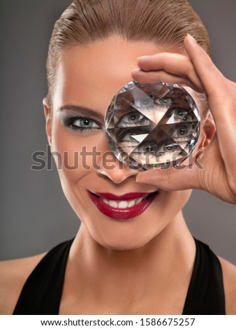 Young woman holding glass prism up to eye, studio shot #1586675257