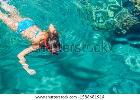 teenage girl enjoy by swimming and snorkeling in Red sea clean water in summer vacation time summer season relaxation background wallpaper picture with empty copy space for your text here #1586681914