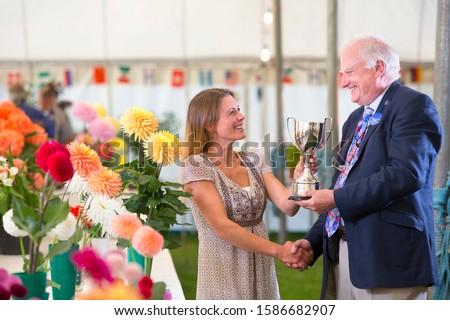 Judge Awarding Trophy At Flower Show #1586682907