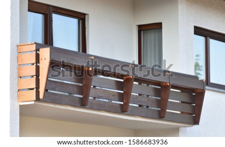 Wooden balcony of a residential building in a residential area of a European city #1586683936