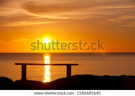 Silhouette of bench with sunset over ocean #1586685640