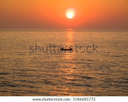 Fishermen in boat at sea with sunset backdrop #1586685772