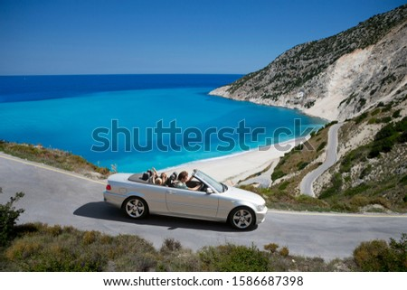 Family driving convertible car along winding coastal road #1586687398