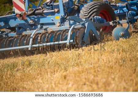 Close Up Of Tractor Ploughing Field Using Disc Plough #1586693686