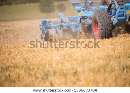 Close Up Of Tractor Ploughing Field Using Disc Plough #1586693704