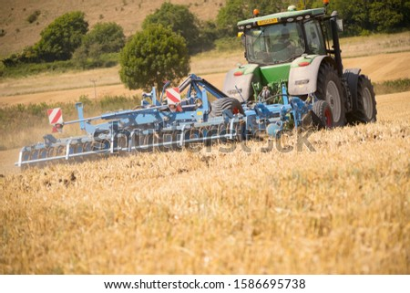 Rear View Of Tractor Ploughing Field Using Disc Plough #1586695738