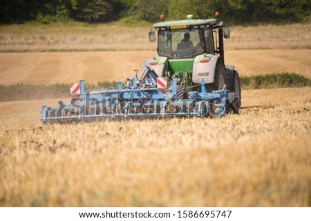 Rear View Of Tractor Ploughing Field Using Disc Plough #1586695747